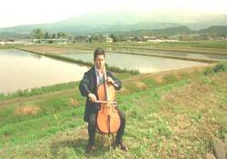 田園の近くでチェロをひいている大悟のイメージ映像
