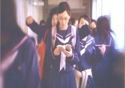 学校の廊下を本を読みながら歩く、主人公・桃子
