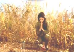 シロの墓を作り、祈る道子