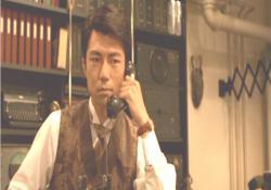 犯行予告のテレビを見ながら電話している明智小五郎