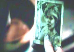 母の遺したテープを見ながら母の写真を見ているコナー