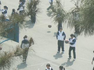 グラウンドで体育の授業にいそしむ学生達~着ている服は校服。学年毎に校服の色が違う。2年生は青、3年生は赤等