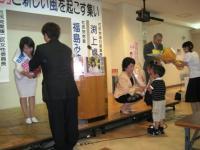 花束を受け取る岡平知子さん、福島党首、渕上副党首