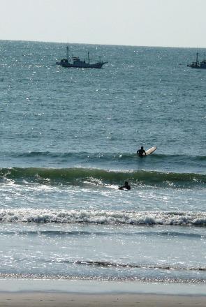 接近するサーファーと漁船