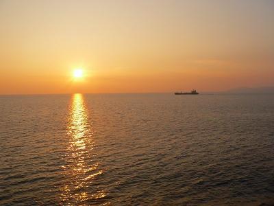写真キャプション=夕日を受けながら佐渡沖を航海する貨物船