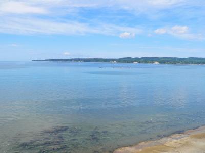 写真キャプション=鏡のように静まりかえる真野湾の向こうに見える二見の岬